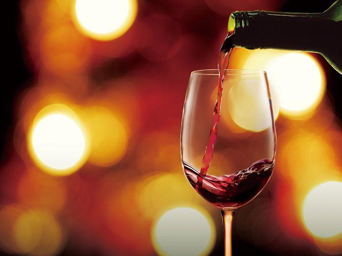 ワインをグラスに注いでいる